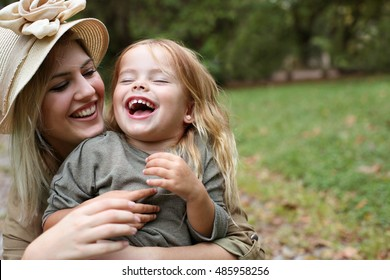 Cheerful mother and her little daughter in the nature.