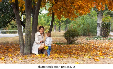 Cheerful mother with her toddler boy playing in autumn park