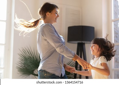 Cheerful mother holding hands with little preschool daughter family having fun in living room jumping listening favourite modern track dancing moving to music. Funny leisure activities at home concept
