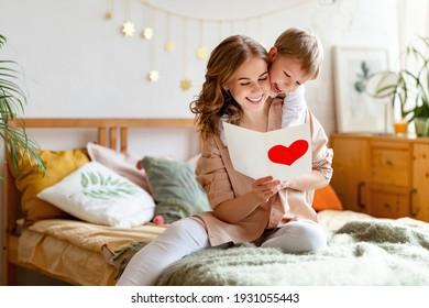 Fröhliche Mutter umarmt Sohn und liest handgemachte Grußkarte mit Herz, während sie sich auf dem Bett während der Feiertagsfeiertage Mütter zu Hause