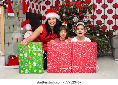 Cheerful mother and kids with Christmas presents in front of tree having fun