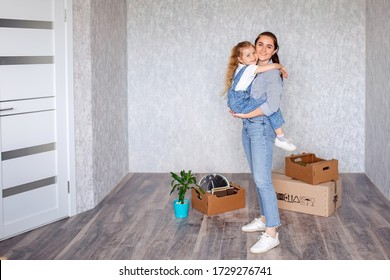 Cheerful mother little daughter is standing in a new apartment. A child has fun with an older sister a nanny or a loving mother active recreation and lifestyle concept.