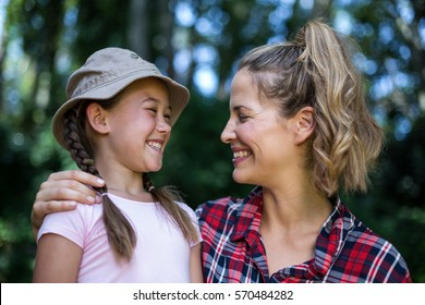 Cheerful mother looking at daughter in back yard