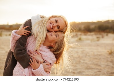 Cheerful mother playing with her little daughter at the beach