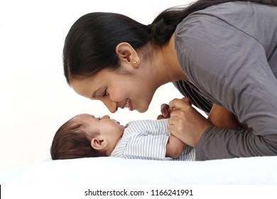 Cheerful mother playing with newborn baby
