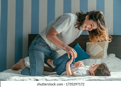 cheerful mother playing with son in bedroom