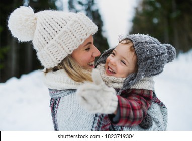 Cheerful mother with small daughter standing in winter nature, laughing.