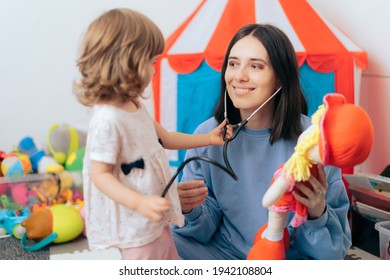 Cheerful Mother with Stethoscope and Doll Playing Doctor. Mom and daughter learning and playing educational game