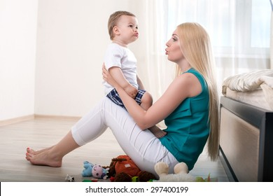 Cheerful mother is teaching her male toddler to talk. She is holding him and sitting on flooring. The mom is looking at her child with love