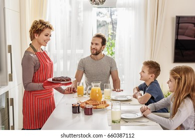 Cheerful mother is treating her kids with self-baked cake. She is holding pastry and smiling. Her husband is sitting and looking at woman with love
