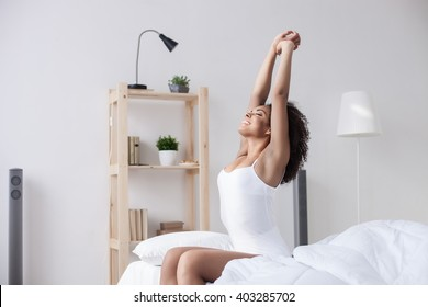 Cheerful mulatto girl is waking up