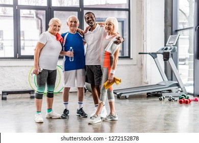 cheerful multicultural senior sportspeople looking at camera and embracing each other at gym