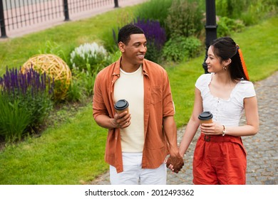 cheerful multiethnic couple with coffee to go holding hands while walking in park