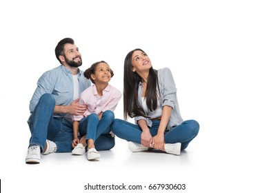 cheerful multiethnic family sitting on floor and looking away isolated on white