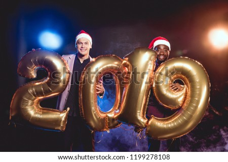 148c3be28475b cheerful multiethnic friends in santa hats holding 2019 new year golden  balloons on smoke and backlit