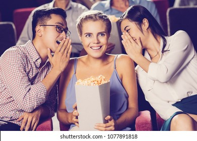 Cheerful multiethnic young friends sitting in cinema and watching movie. Asian woman and man whispering to their laughing Caucasian friend holding popcorn