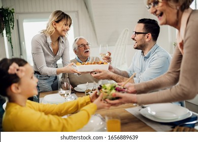 Cheerful multi-generation family having lunch together at home. Women are serving food.