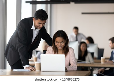 Cheerful multiracial coworkers, middle eastern ethnicity male and african black female looking at computer screen working together in contemporary coworking space with other millennial business people