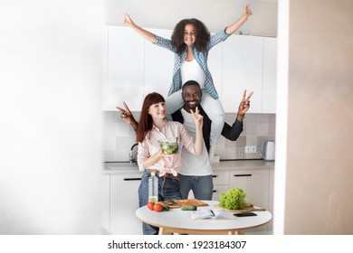 Cheerful multiracial family cooking salad together in modern kitchen. African dad holds her cute teen daughter on shoulders and posing with his european wife to camera with peace sign