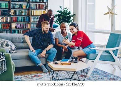 Cheerful multiracial group of friends laughing a funny videos from social networks on mobile phone,smiling male and female hipsters viewing funny photos on smartphone resting together at home