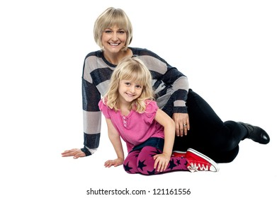 Cheerful mum and daughter sitting on studio floor. Facing camera and flashing smile.
