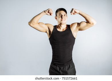 Cheerful muscular guy posing in front of the camera.