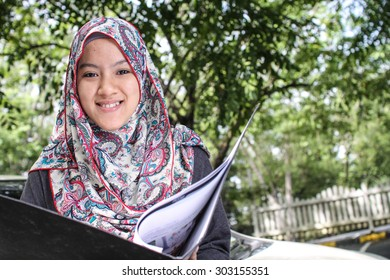 cheerful muslim business woman holding a file