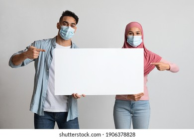 Cheerful muslim couple pointing at blank advertisement board, arab man and islamic woman in hijab holding white placard with copy space for your offer or information over gray studio background