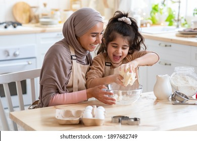 Cheerful Muslim Mom In Hijab And Her Little Daughter Having Fun At Home, Baking Pastry In Kitchen Together, Kneading Dough While Preparing Cookies, Enjoying Cooking Homemade Food. Closeup Shot