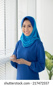Cheerful Muslim woman texting with smartphone