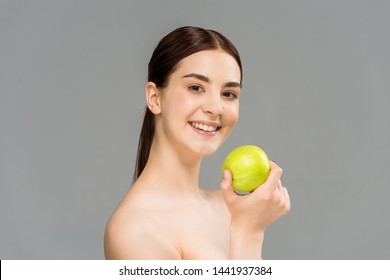 cheerful naked woman smiling while holding green apple isolated on grey