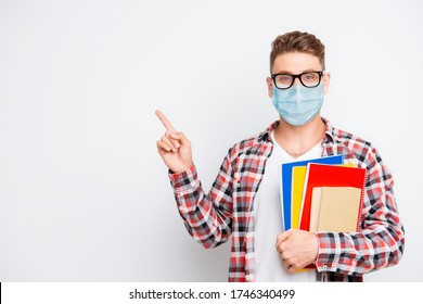 Cheerful nerd student holding book and educational materials pointing on a copyspace showing information idea wear medical safety face mask, remote distance online education concept