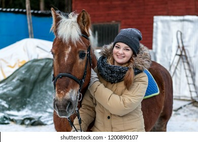 Cheerful nice girl with a horse. Country Equestrian Club. Winter trip out of town