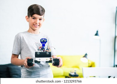 Cheerful nice little boy holding a robot while preparing for engineering competition