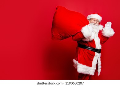 Cheerful nice peaceful Santa in eyeglasses wishes you merry Christmas waving hi hello holding keeping delivering huge sack with toys isolated over bright vivid red background