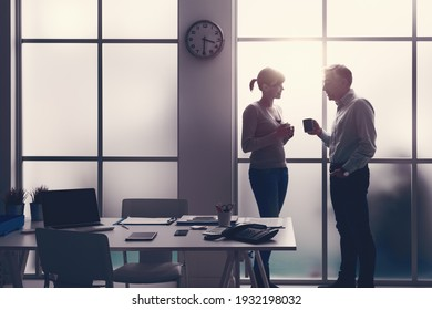 Cheerful office workers relaxing, having a coffee break and chatting together, they are standing in front of the window and holding a cup