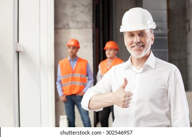 Cheerful old architect is giving his thumbs up. His project was done perfectly. The man is smiling and looking at the camera happily. Two builders are standing behind him and relaxing
