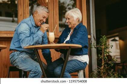 Cheerful old couple sitting at cafe having a coffee. Senior man and woman sitting at restaurant table talking with cold coffee on table.
