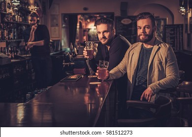 Cheerful old friends drinking draft beer at bar counter in pub