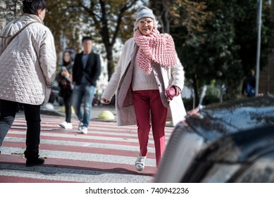 Cheerful old lady crossing the road in city