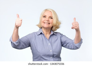 cheerful old woman in colored sweater showing thumbs up gesture