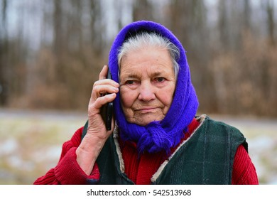 Cheerful old woman receiving some bad news over smartphone. Sad senior woman in village using mobile phone.