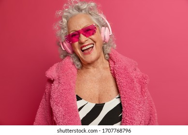 Cheerful old woman with upbeat mood, wrinkled skin, has fun on pension, listens music in modern stereo headphones, wears trendy sunglasses, isolated on pink background. Retirement life concept