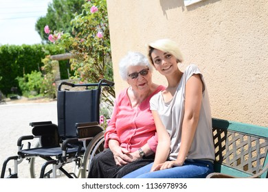 cheerful old woman in a wheelchair with her young granddaughter outdoor in hospital