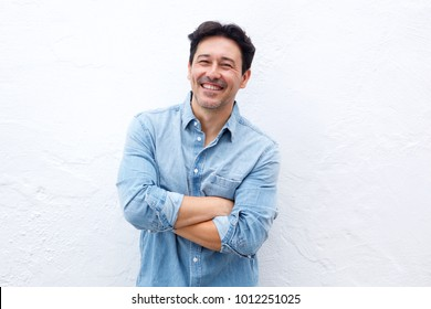 Cheerful older man standing with arms crossed on white background