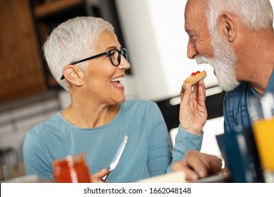 Cheerful older woman with a short gray hair feeds her attractive man husband. Morning just for us