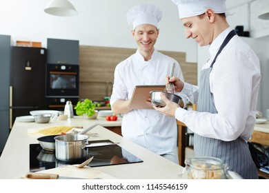 Cheerful optimistic handsome young chef satisfied with students work writing in sketchpad and laughing while talking to intern in apron mixing food in bowl in commercial kitchen.