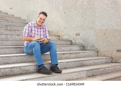 Cheerful optimistic young student making notes in sketchpad and looking at camera. Positive handsome man in jeans and casual shirt sitting on stairs and planning day. Freelancer concept