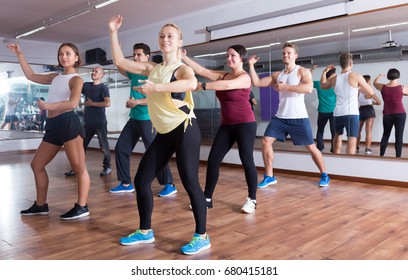 Cheerful ordinary adults dancing bachata in dance studio