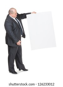Cheerful overweight stylish business man in a suit holding up a blank white sign and pointing to it with his finger on a white studio background